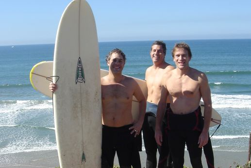 three-shirtless-guys-on-beach-with-surfboards